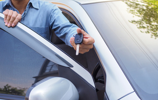 Car rental client returning key of vehicle