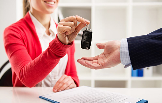 Rental representative giving hired car keys to customer