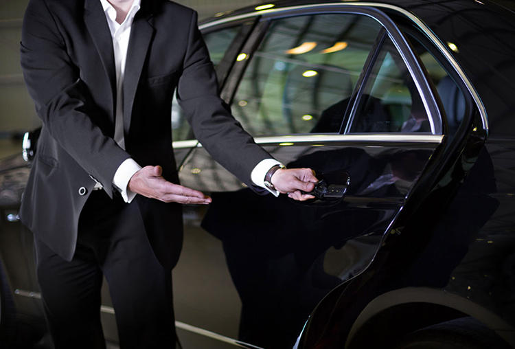 A Chauffeur opening the door of the car for the customer
