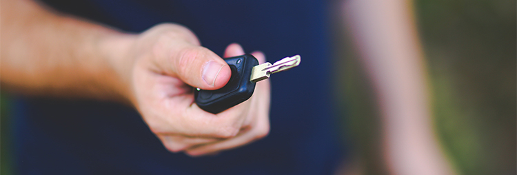 Staff of rent a car company giving car key to customer