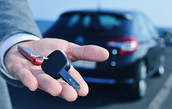 Car rental representative offering you the key of your rented car