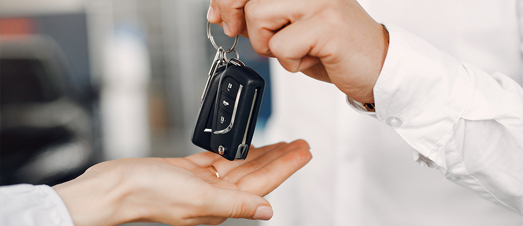 Man's hand giving the car key to woman's hand